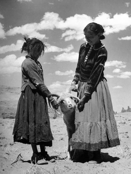 Native American Indian children playing with ram.