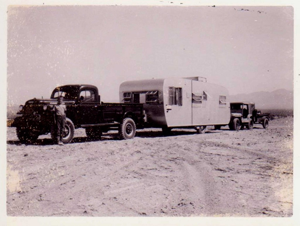 "Our prospecting outfit on the way to Moab!  A brand new 1955 Dodge C3PW Power Wagon pulling a new 24' Boles Aero travel trailer.  Dad had them mount a water tank on top to increase our water capacity.  Behind that is our 1951 Willys CJ3 pulling a military jeep trailer with a 300 gallon water tank.  The first night out of California Dad pulled off the highway onto what appeared to be firm sand.  He buried the Dodge to the axles in the morning trying to get out.  Then hitched the Jeep to the front end and buried that as well.  Finally got the Jeep out, disconnected the Boles and buried a ""dead man"" 12x12 timber in order to get the Power Wagon out.  Not sure how he got the trailer back out, must have winched it over to firmer ground and reattached it."