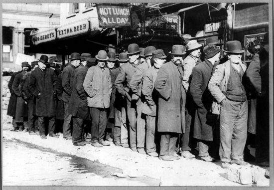 Bowery men waiting for bread in breadline.