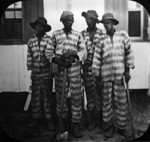 Floridian convicts leased to harvest timber in the mid-1910s. By Unknown - Public Domain.