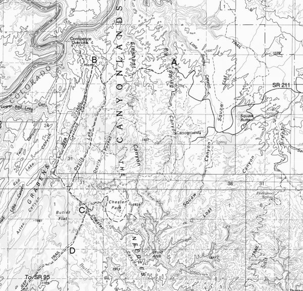 A U.S. Geological Survey map showing planned roads in Canyonlands. The proposed five Needles District roads are indicated with a dashed line emanating from 'A' where the road to Big Spring Canyon currently ends and the bridge was to be built. The junction of the road to the Confluence overlook is labeled with a 'B.' The entry by road to Chesler Park is marked with a 'C.' The Kigalia Parkway south to Beef Basin to State Road 95 is marked with a 'D.' — U.S. Geological Survey