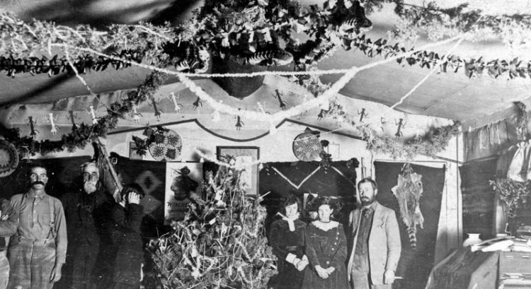An early-day Christmas celebration (ca. 1911) in the Wetherills' home. Louisa to the right of the tree, daughter Georgia to the right of her, and son Ben (hiding his face) to the left of the tree. The man to the left of Ben is Justus Tompkins, John Wetherill's uncle. The other men are unidentified guests—maybe prospectors.