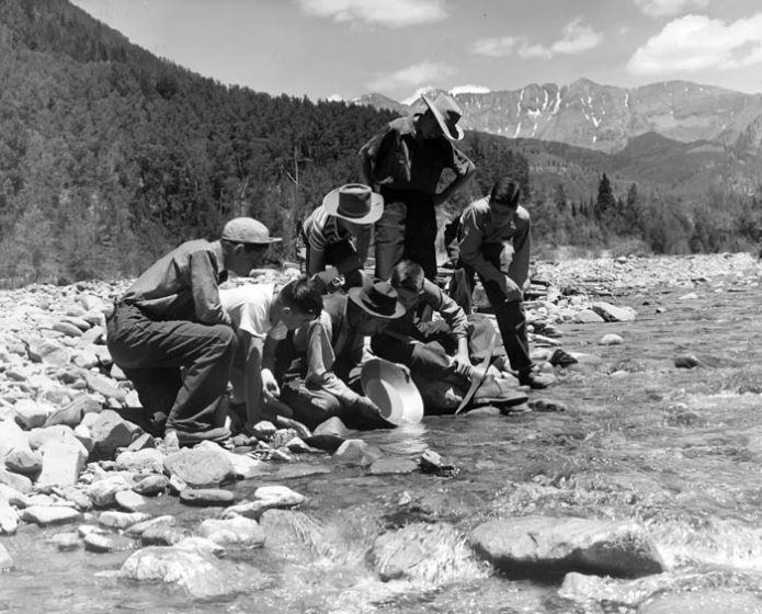 Prospector Marshall Long showing boys how to pan for gold in La Plata Creek