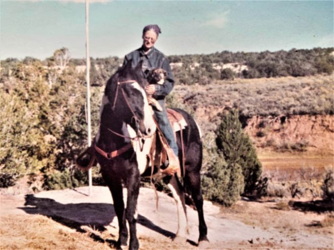 1974 Becky Brock on Tsetso, Pete's horse, at Kane Gulch Ranger Station flagpole looking east across Highway U-261. Becky's photo